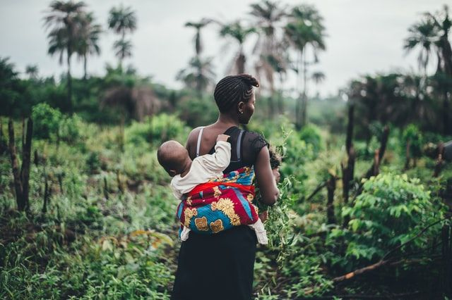 Baby clinging on back of mother working in Africa